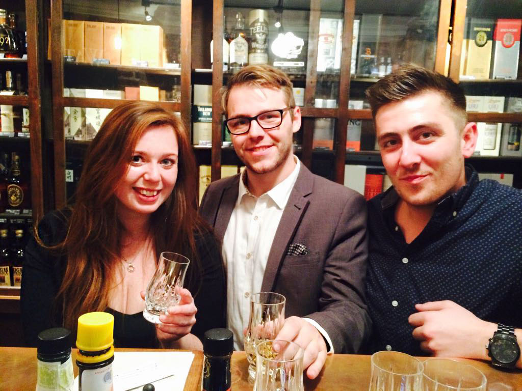 3 people sitting at the bar of milroy's with whisky bottles in the background