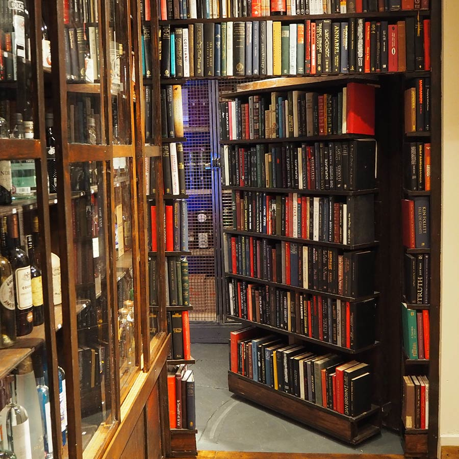 bookcase that leads to stairway milroy's whisky bar