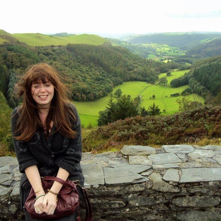 Bryony sat on a stone wall with picturesque hills and scenery behind