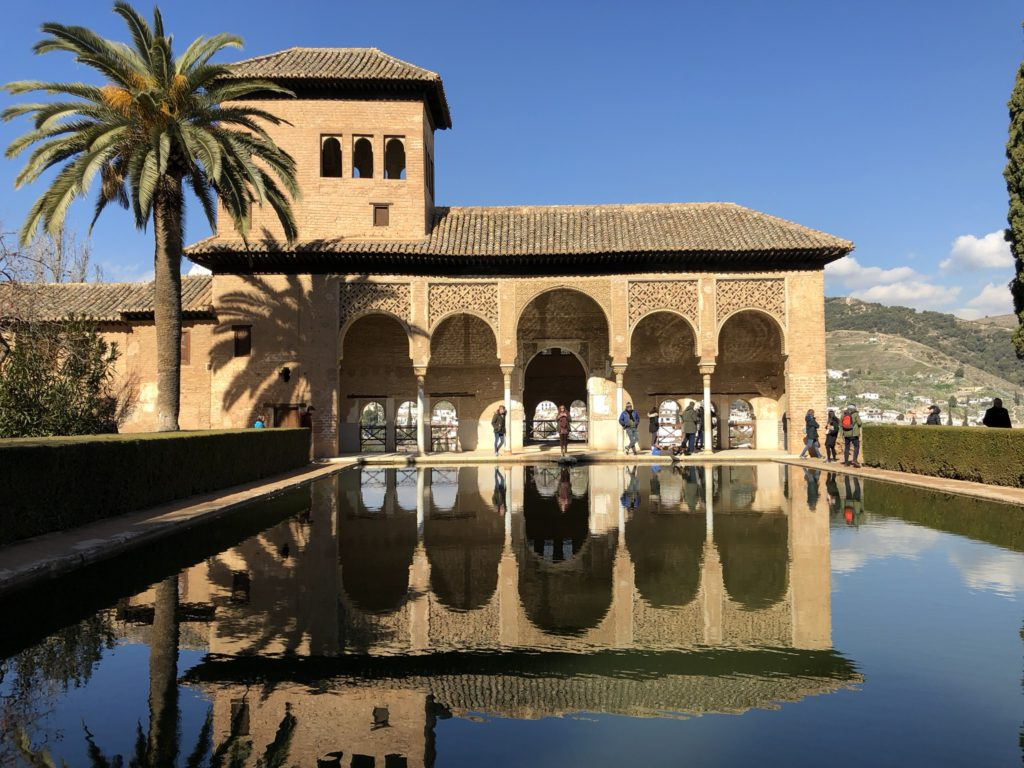 Alhambra palace garden architecture and pond water reflection with palm tree