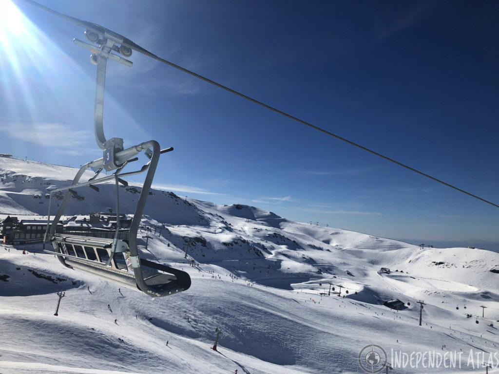 snowboarding in spain, skiing in spain, snowboarding the sierra nevada mountains, chair lift, blue skies, snow