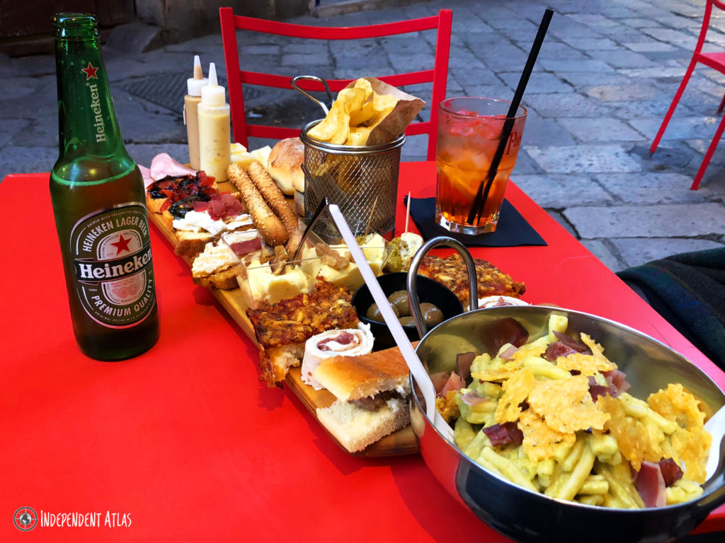 Huge plates of food and a beer on a red table, Palermo street food, Street food in Palermo,