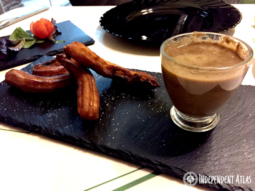 3 potato churros on a slate plate with a glass cup of gravy and a salad in the background, Best places to eat in Santa Pola, Tapas, Costa Blanca