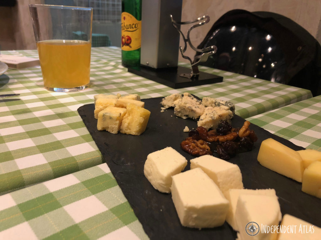 A slate cheeseboard with 4 different types of delicious cheeses and a pile of nuts and berries in the middle, green check table cloth, Best places to eat in Santa Pola, Tapas, Costa Blanca