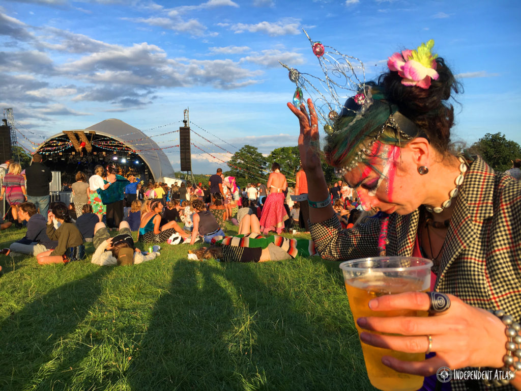 Wilderness Festival, Festivals on a budget, Girl with pint of cider and wilderness stage in the background