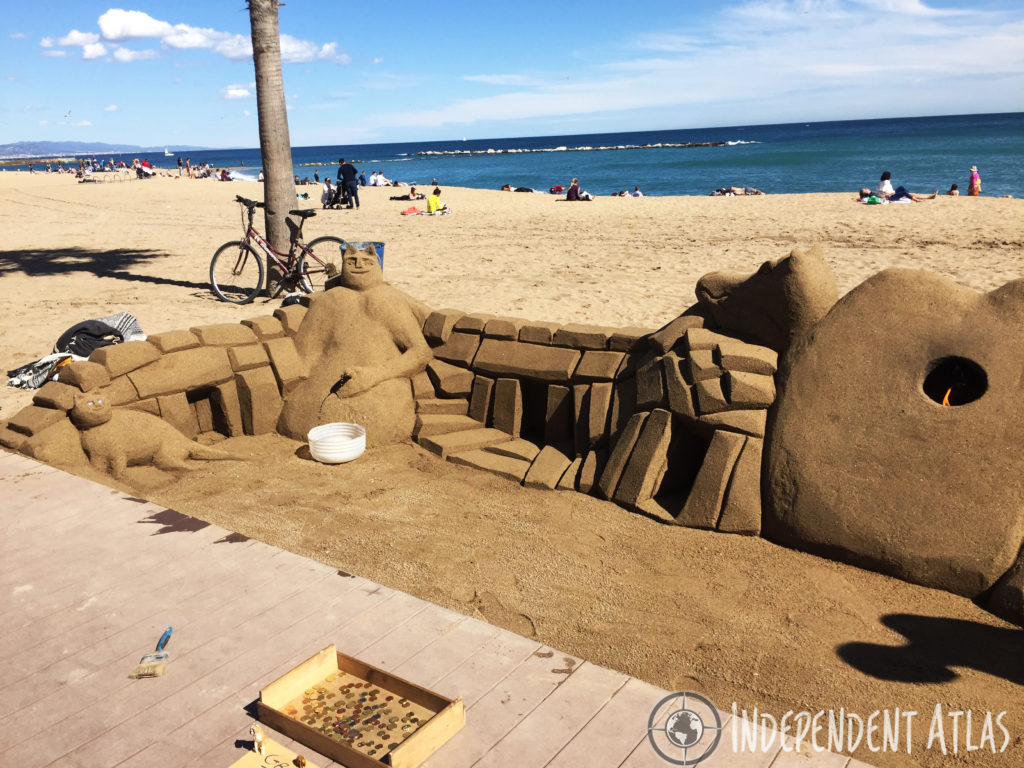 A day in Barcelona, a sand sculpture with figurine weeing(?!) and sand cat with the sea in the background at Barceloneta beach