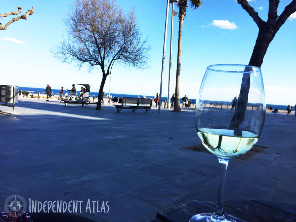 A day in Barcelona, A glass of white wine on a table looking out over Barceloneta beach promenade