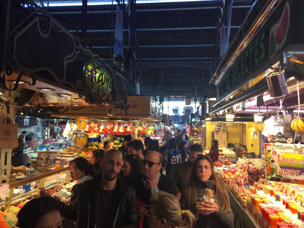A day in Barcelona, busy indoor market full of people. Fruit, veg, smoothie stalls line the walkways