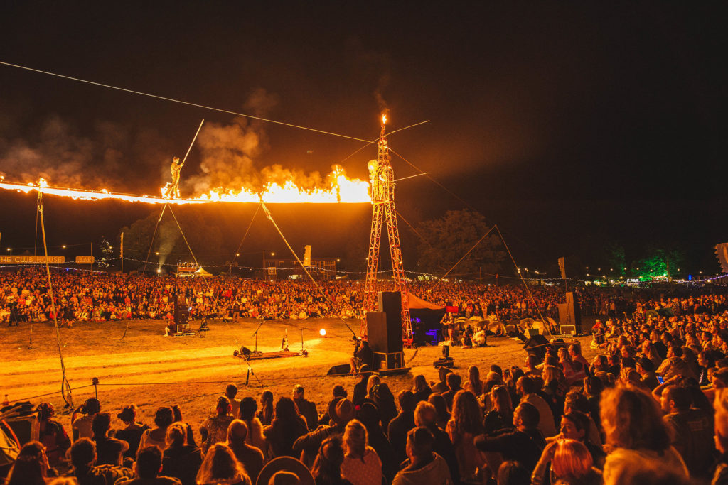 Wilderness Festival, festivals on a budger photo of crowd at night with fire trapeze up a vove