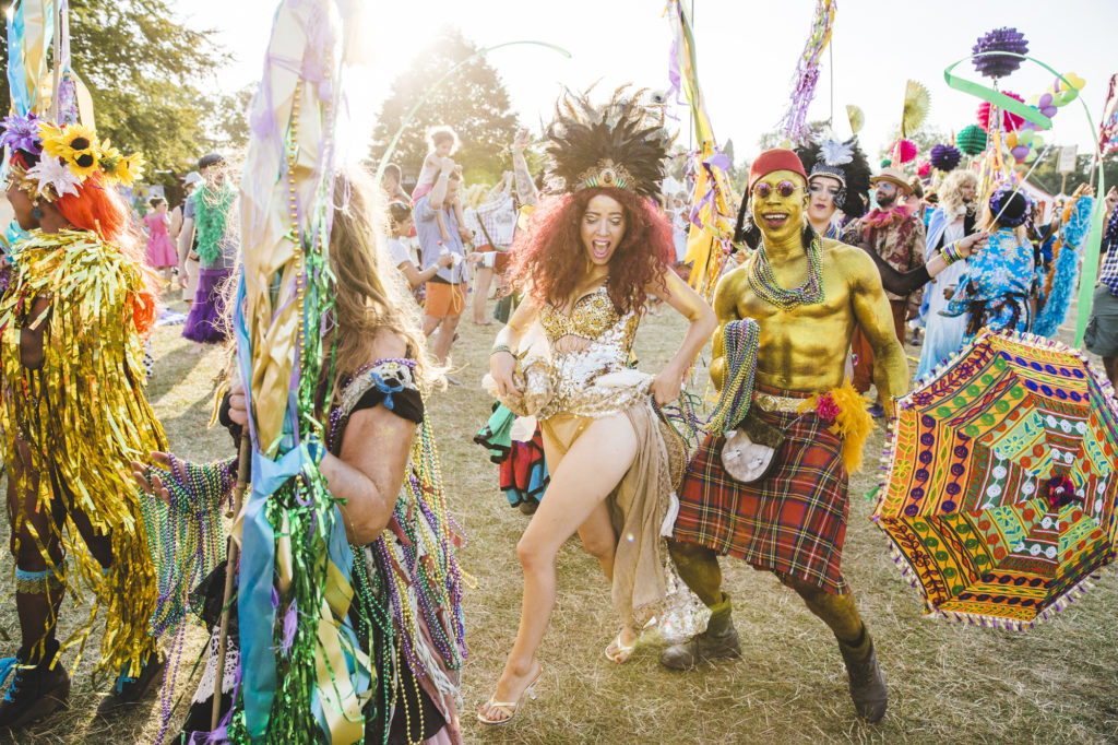 Wilderness Festival, festivals on a budget, revellers, goddess in a gold crown and sparkly outfit, man painted gold in kilt with a brolly