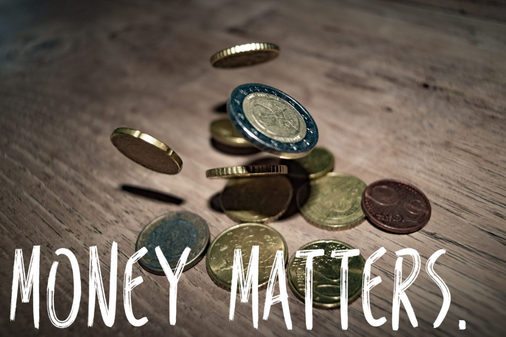 How to budget for travel, Budgeting while travelling, Euros dropping onto a wooden table with the words Money Matters. in white