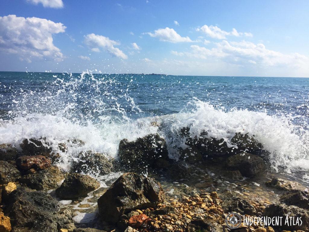 Waves crashing over rocks with a bright blue sea and sky, Irish bar in Santa Pola