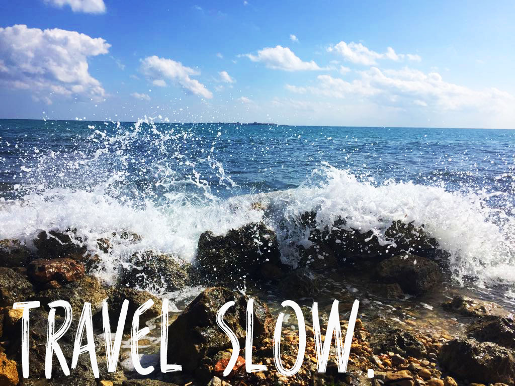 How to budget for travel, Budgeting while travelling, Waves breaking on the beach with Travel Slow. written in white